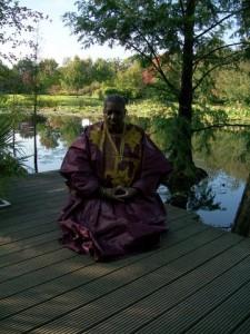 Roshi Kitabu Turner meditating at a Lotus Pond in Germany.
