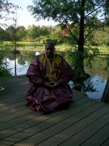 Roshi Kitabu Turner meditating at a Lotus Pond in Germany.